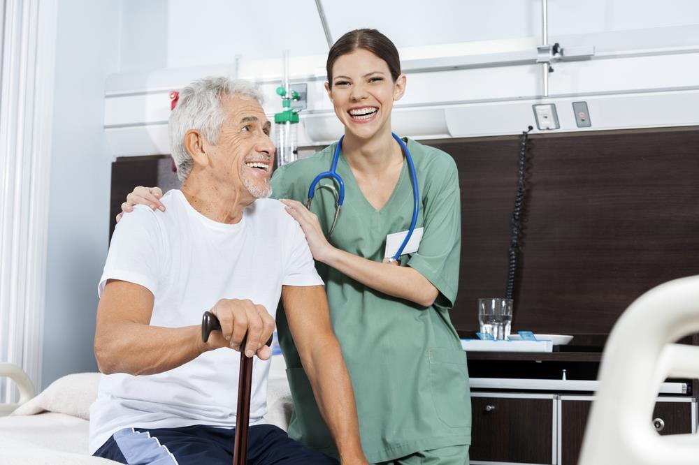 smiling nursing assistant and patient together in a hospital room