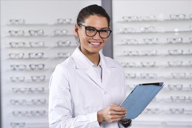 female optometrist at work in front of a display of glasses