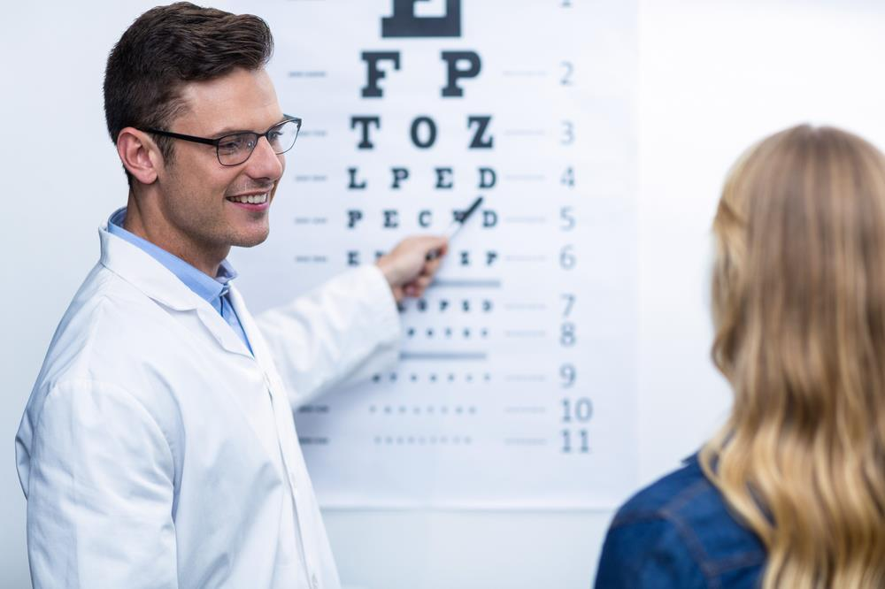male optometrist running a vision test on an adult patient