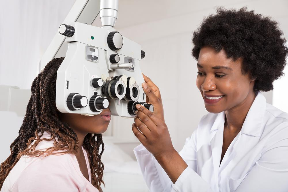 female optometrist completing an eye exam on an adult patient
