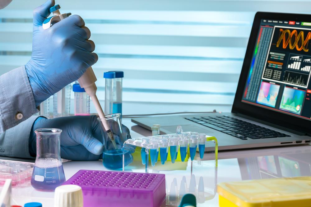 analytical chemist working on samples in the lab while looking at data on a laptop