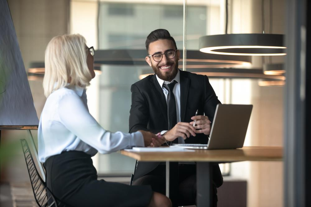 Boss completing a stay interview with her smiling employee
