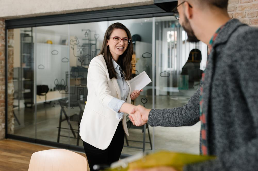 Job candidate and hiring manager shaking hands before interview