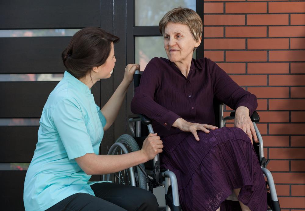 volunteer nurse assisting an elderly patient outside of a medical facility