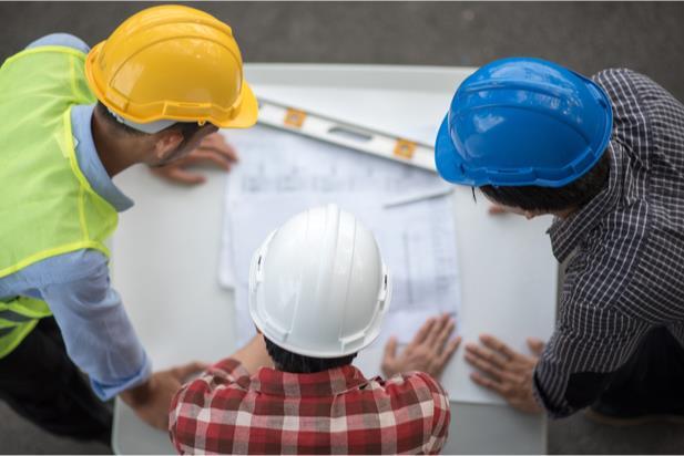 three civil engineers looking at a diagram