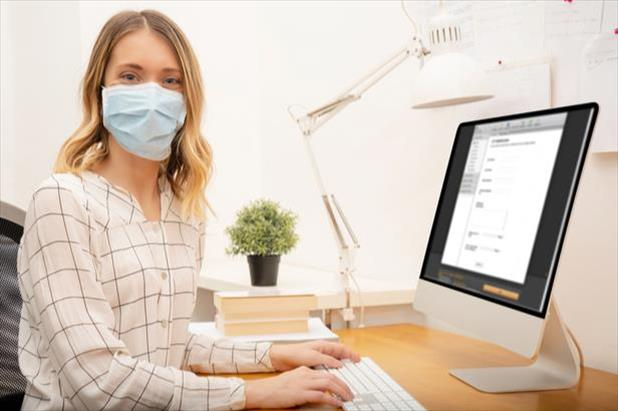 woman writing a job ad in a mask