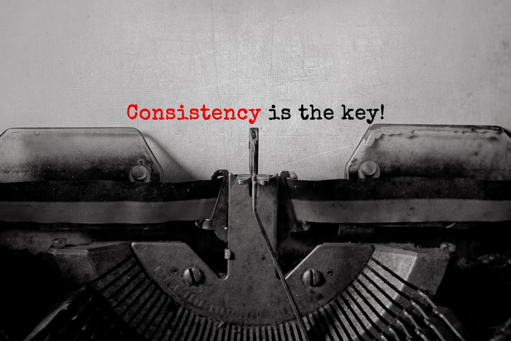 "Old typewriter with page inserted reading ""consistency is the key!"""
