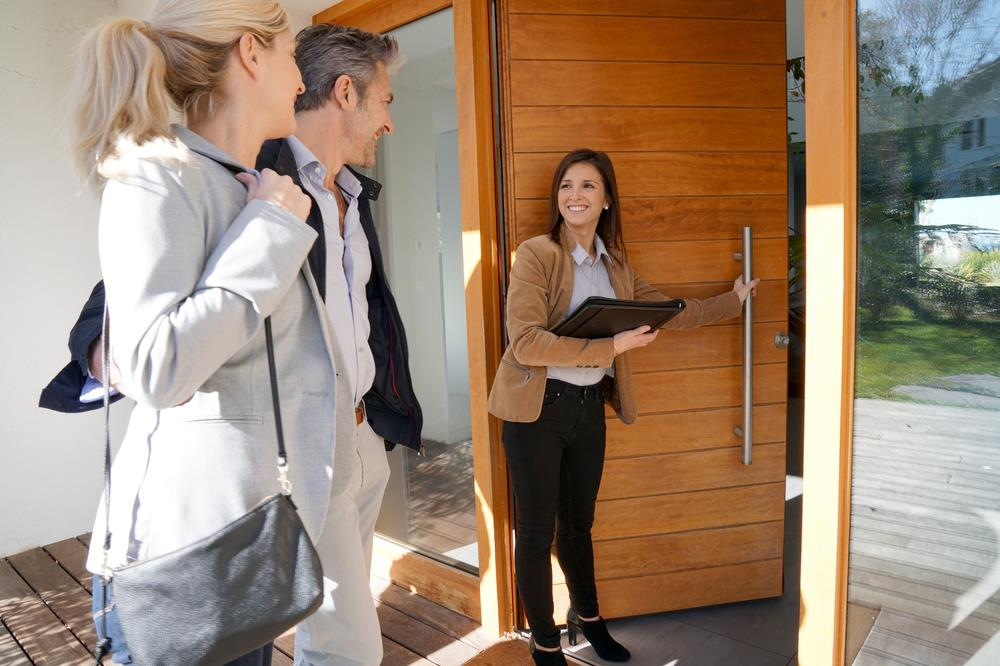 Residential real estate agent showing couple around a new home
