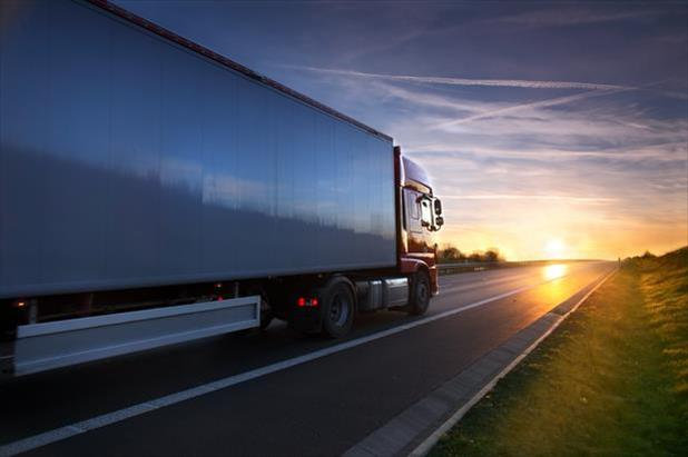 Long haul truck traveling across state lines as the sun sets
