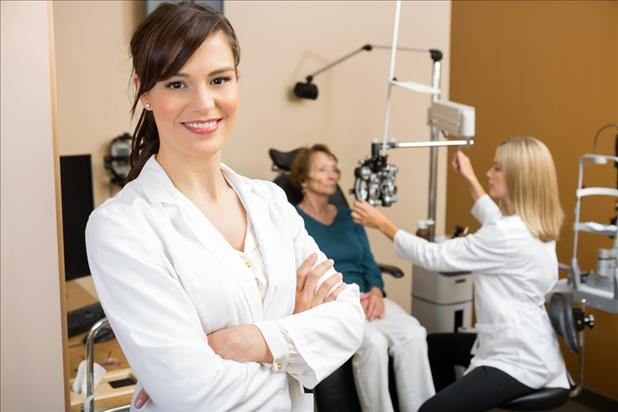 optometry mentor with her mentee in the background caring for a patient