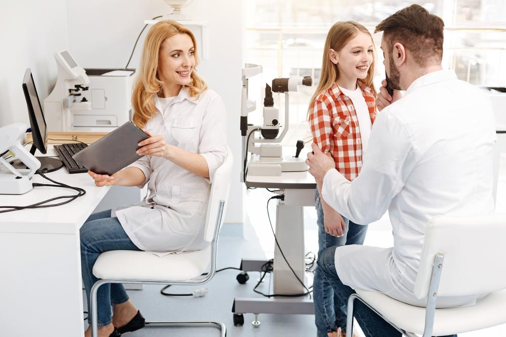 new grad optometrist with his mentor and a pediatric patient