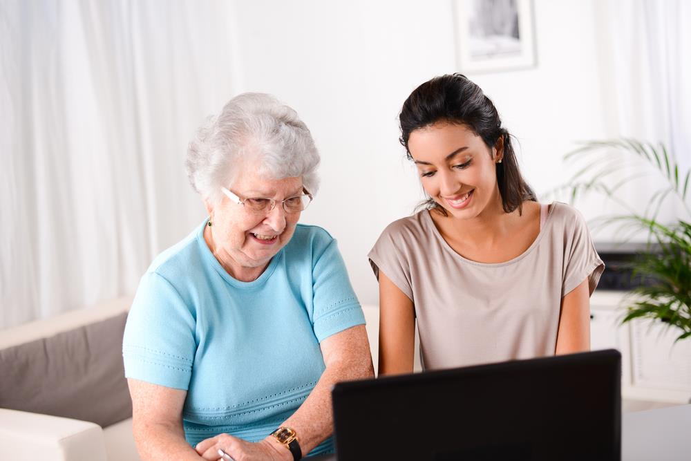 female social worker helping elderly woman use computer
