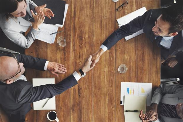 People shaking hands across table at business event
