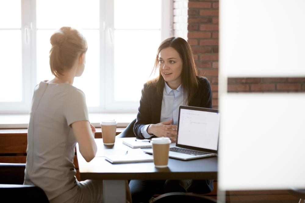 Woman having a private conversation with her smiling boss