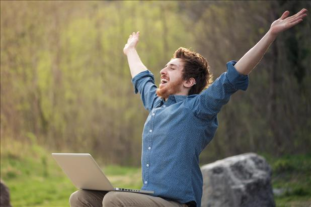 enthusiastic job seeker with lap top celebrating success
