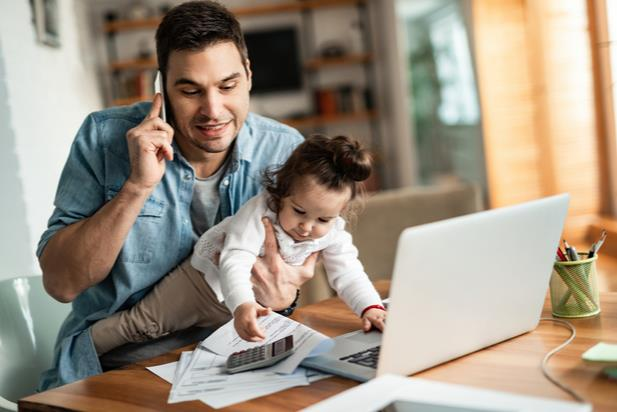 man working from home with his child