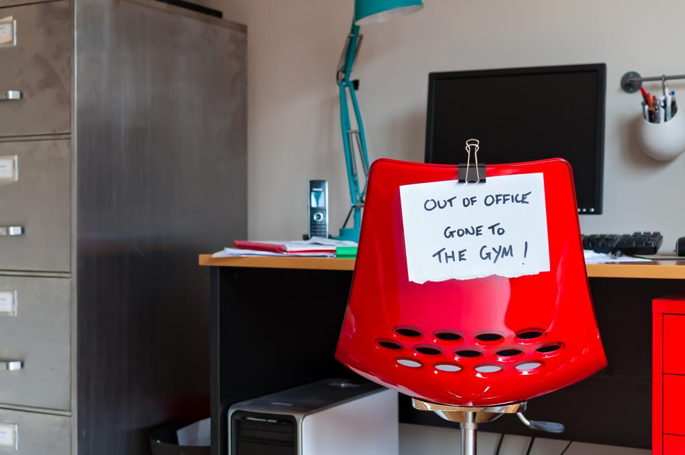 "employee's desk chair with ""out of office gone to the gym"" message on the back"