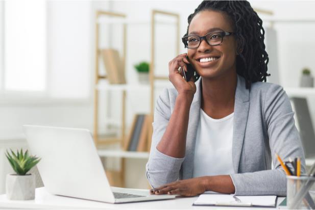 woman talking on phone at laptop