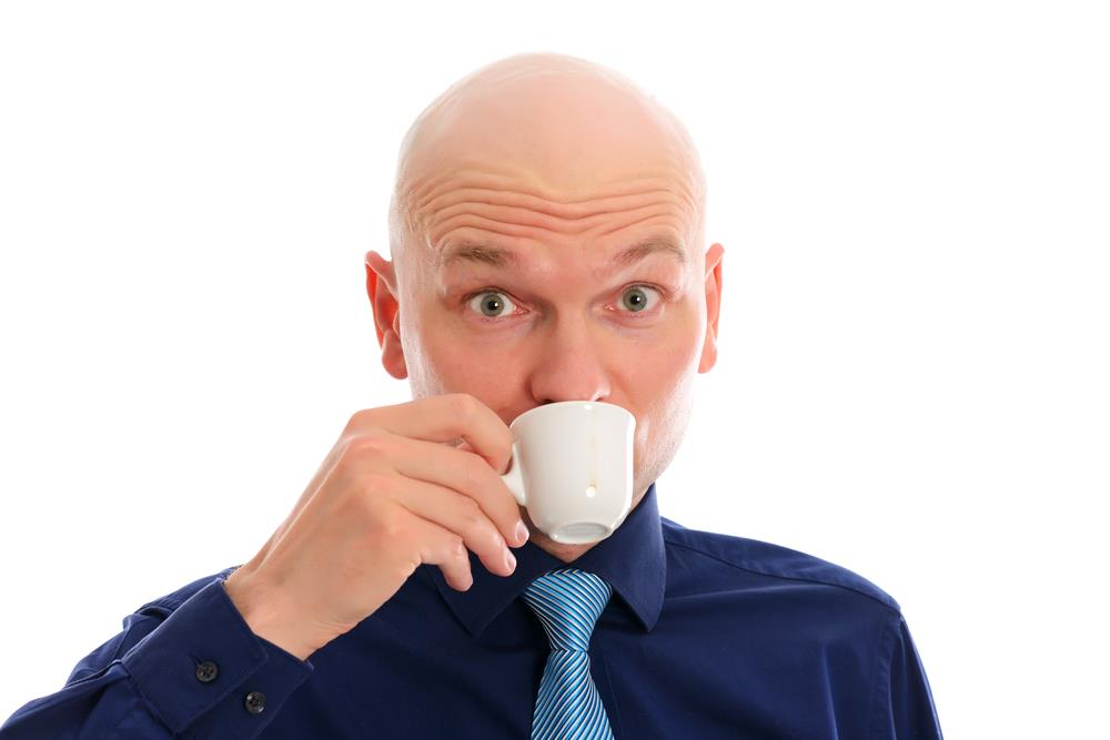 bald man drinking a shot of espresso