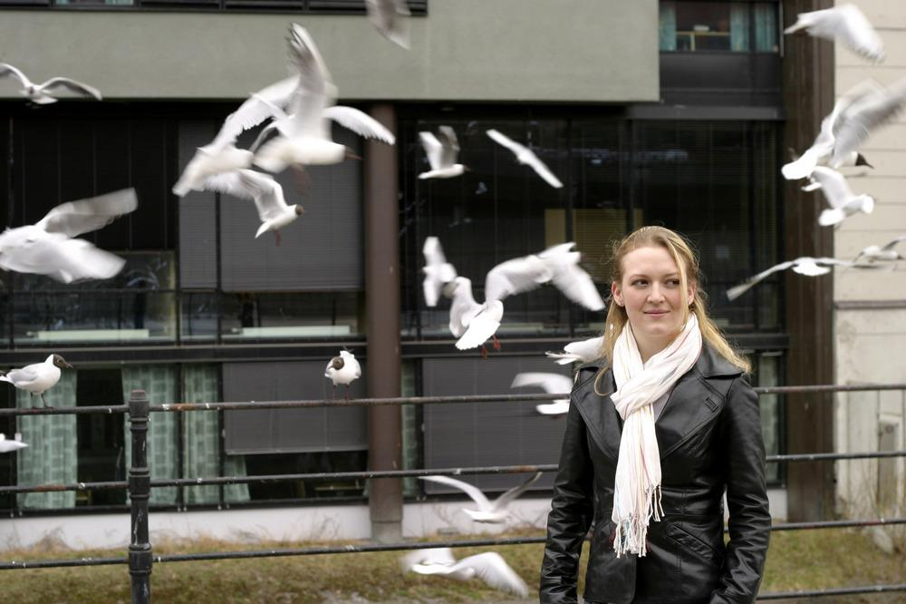 woman standing in a flock of birds