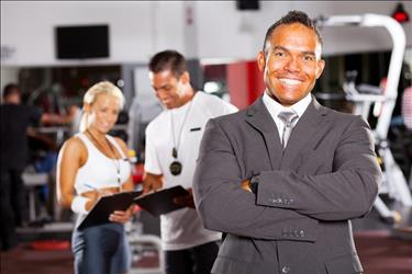 smiling gym manager with staff in the background