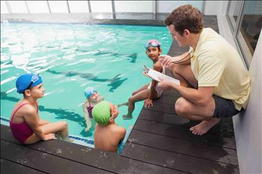 swim instructor talking to students in a pool