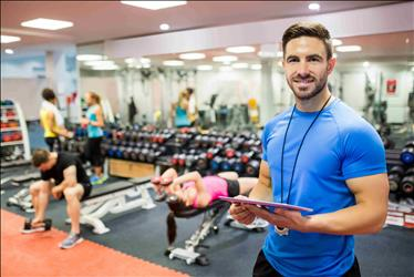 Personal trainer smiling with people exercising in the background