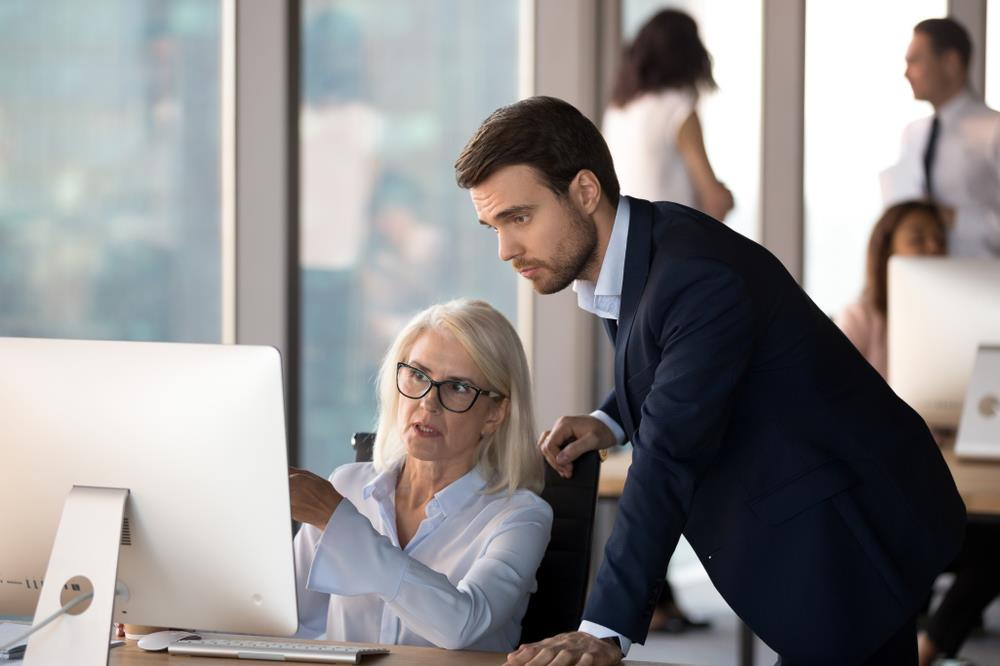 accountant showing her coworker financial data on her computer