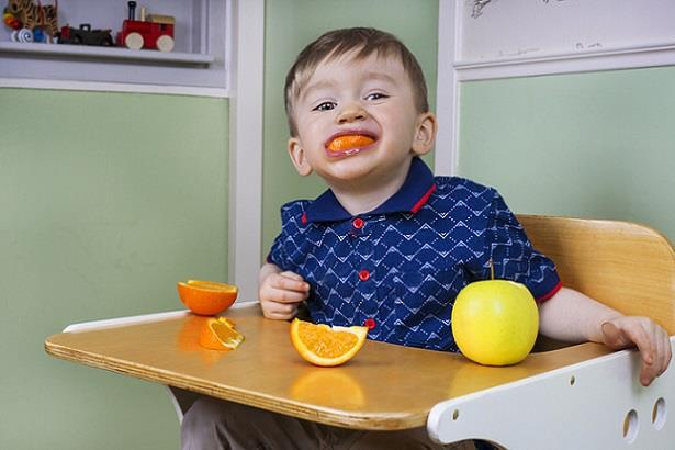 Young child eating oranges at lunchtime