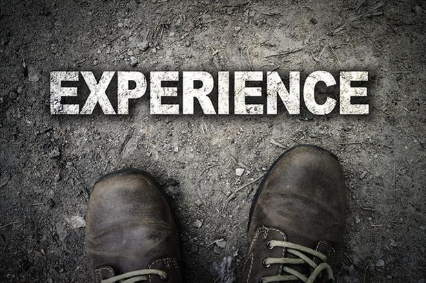 "View of shoes with ""experience"" written in chalk on asphalt"