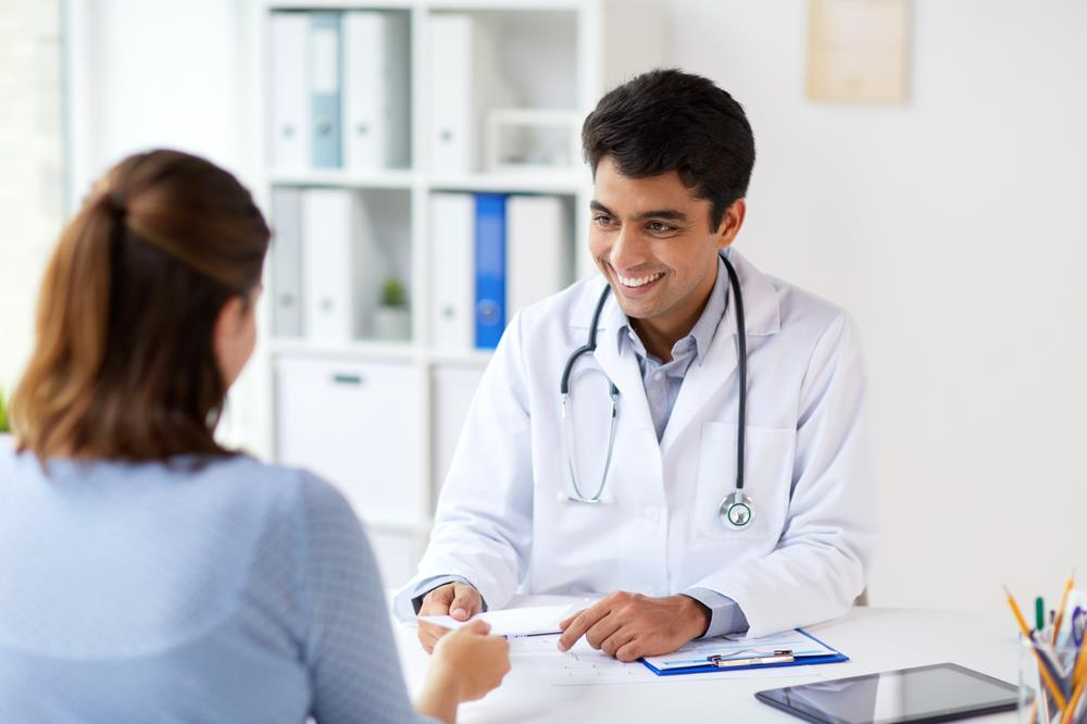 smiling physician meeting with a patient