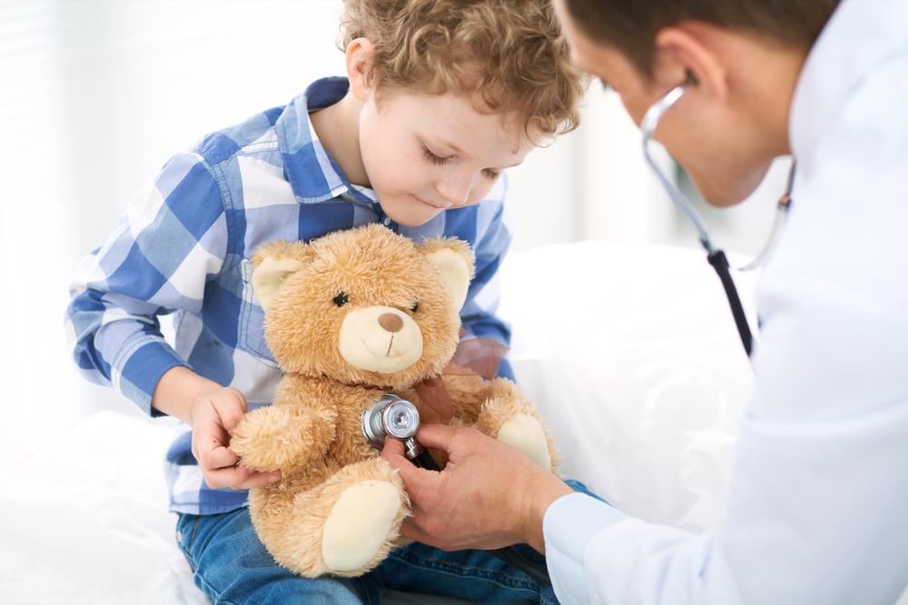 pediatrician pretending to check the heartbeat of her patient's teddy bear