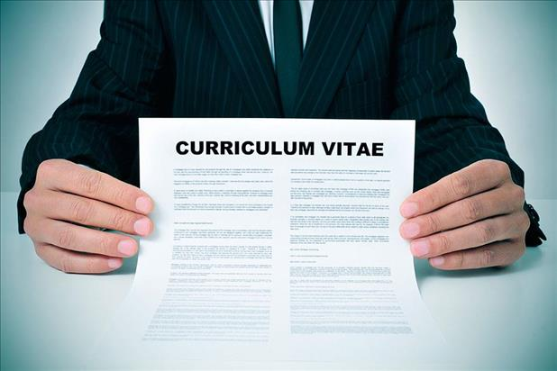 Professional in suit holding up his curriculum vitae