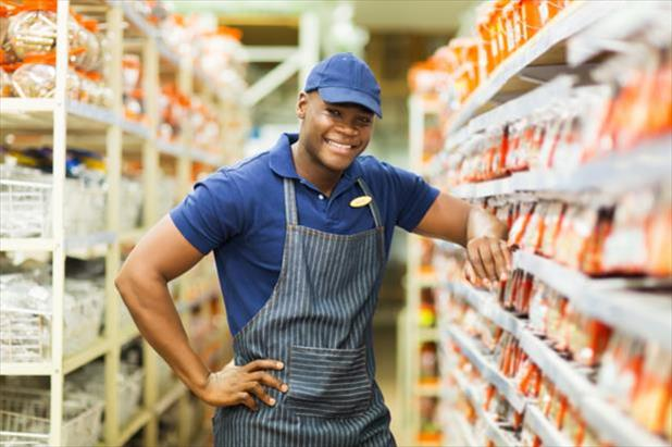 Hardware store employee smiling next to merchandise