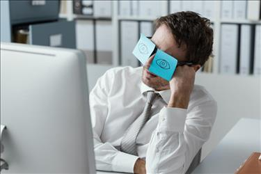 job seeker at his desk with silly post it notes on his eyes