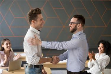 employee shaking hands with his supervisor after being promoted from part-time to full-time
