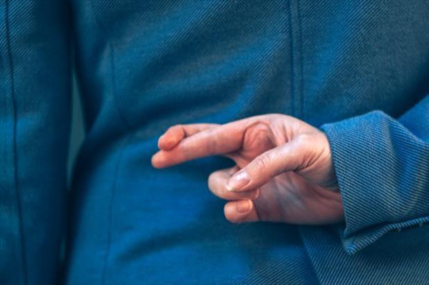 Job seeker with crossed fingers, hiding lies on their resume