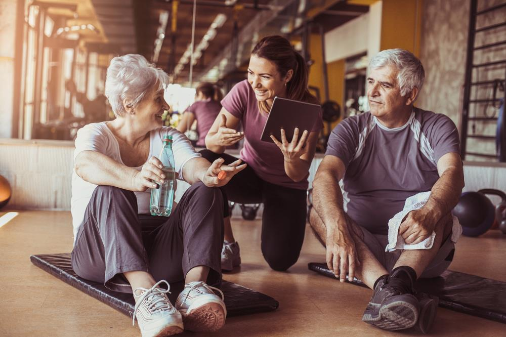 Personal trainer working with two older clients