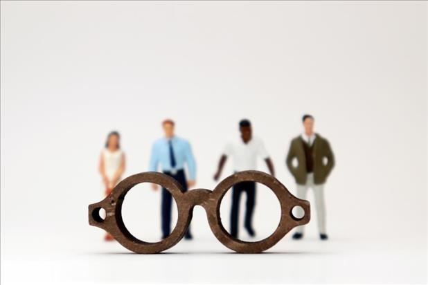 a pair of glasses in front of four job candidates