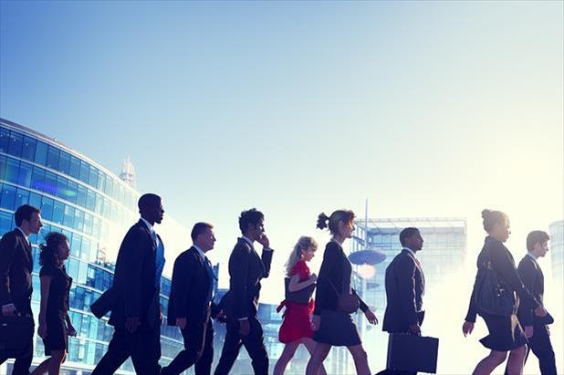 Group of confident job seekers walking with modern buildings in the background
