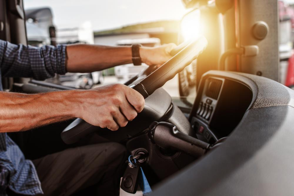 close-up of a cdl truck driver's hands on the wheel