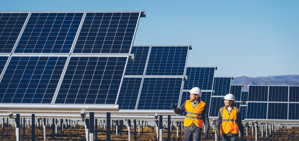 two solar technicians walking in a solar field