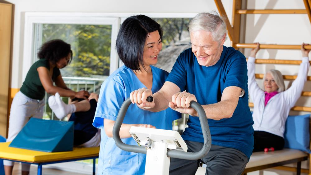 caregiver helping an elderly patient exercise