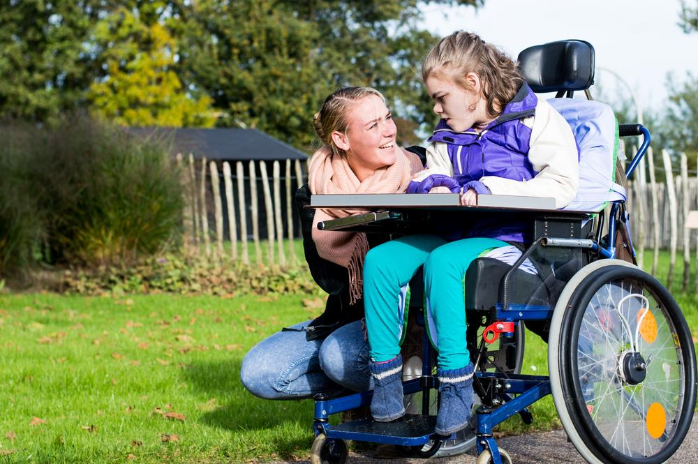 caregiving professional helping a young girl with a disability