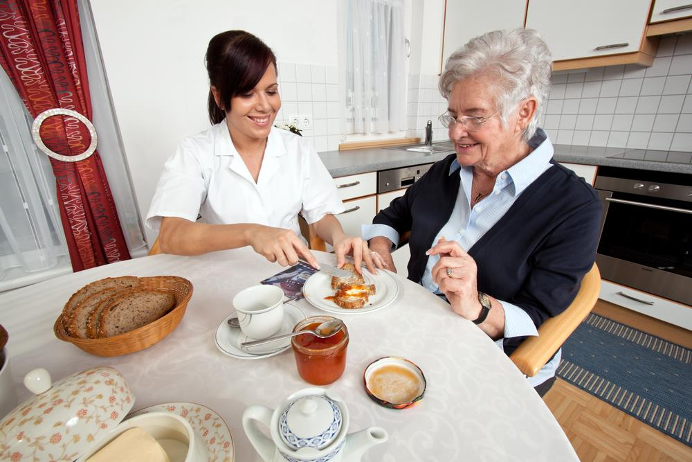 caregiving professional helping an elderly patient with breakfast in her home
