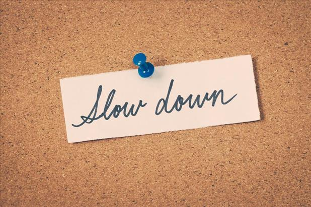 "bulletin board with note pinned on it saying ""slow down"""