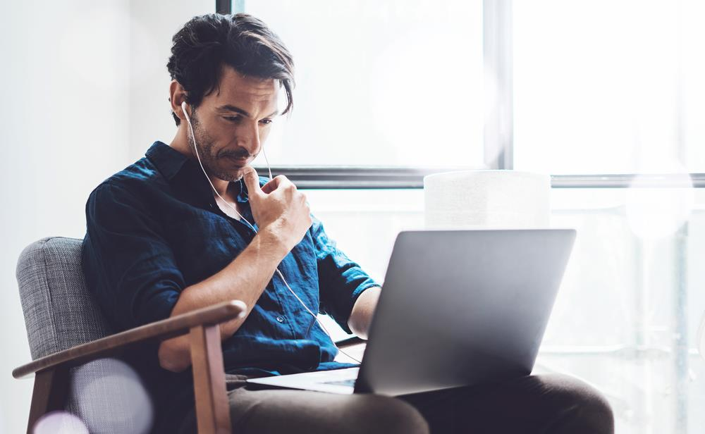 Professional wearing headphones and thinking while looking at laptop