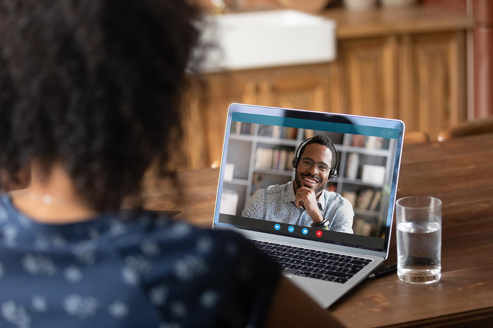 Woman interviewing a man using videoconferencing/Zoom