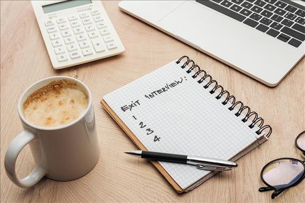 Handwritten Exit Interview planning in a spiral-bound notebook