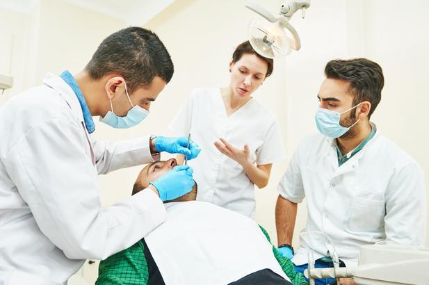 Allied dental educator overseeing patient examination